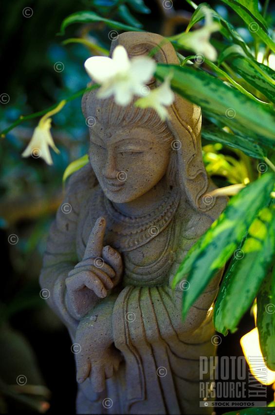 Kwan yin stone statue with orchids at Paleaku gardens, South Kona, Big island