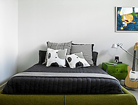 The black and white bedding contrasts with the green felt bedframe of this teenagers bedroom