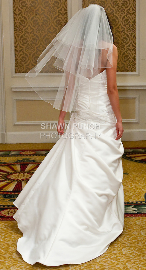 Model walks in a Musetta Dress - Ivory regal satin strapless gown with beaded English net motifs on tucked body and asymmetrical dropped pick-up skirt with sweep train, by from the Watters Fall 2010 Bridal Collection, during the Wedding Channel Couture Show Fall 2010.