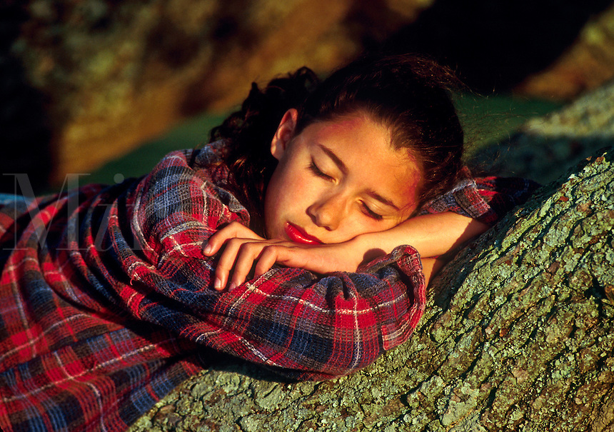 Girl rests on a tree trunk.