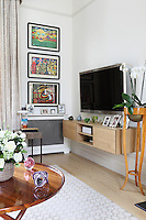 A row of colourful paintings hang above family photographs in the living room