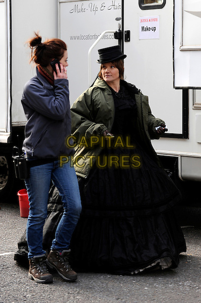 """JESSICA STEVENSON .On the set of """"Burke and Hare"""", Lincoln's Inn, London, England..March 8th, 2010.film movie full length black coat gown dress green jacket top hat costume .CAP/IA.©Ian Allis/Capital Pictures."""