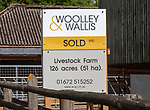 Estate agent Woolley and Wallis property sold sign at livestock farm near Potterne, Wiltshire, England, UK