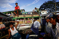 Drivers of different vehicles wait for passengers to arrive by ferry from Yangon to Dallah township September 18, 2012. Dallah Township, a short ferry ride across the river, is the place where the big city touches the province. Thousands of daily migrants cross the river to Dallah using dangerous long tail boats and cheap government operated ferries. As soon as a ferry unloads passengers hundreds of rickshaws, motorcycles, pick-up trucks and small busses start their loud performance to get people on-board. They donÕt leave on schedule but only when not even a small bag or another new born baby canÕt fit inside or on its roof.    REUTERS/Damir Sagolj (MYANMAR)