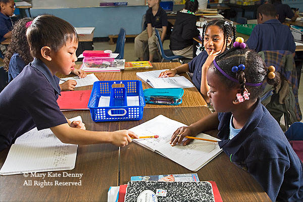 Vietnamese male second grader points to paper to help African American girl with braids at their desk in classroom in Louisiana
