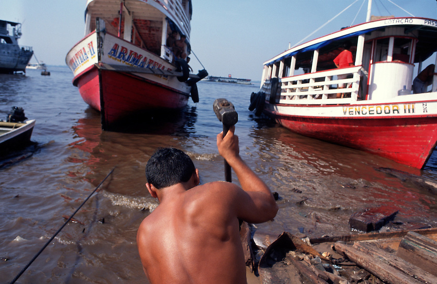 Boat repairmen work on the muddy shore of the Amazon port city of Manaus. A thousand miles up river from the coast, most travelers and goods come and go from the city by boat.