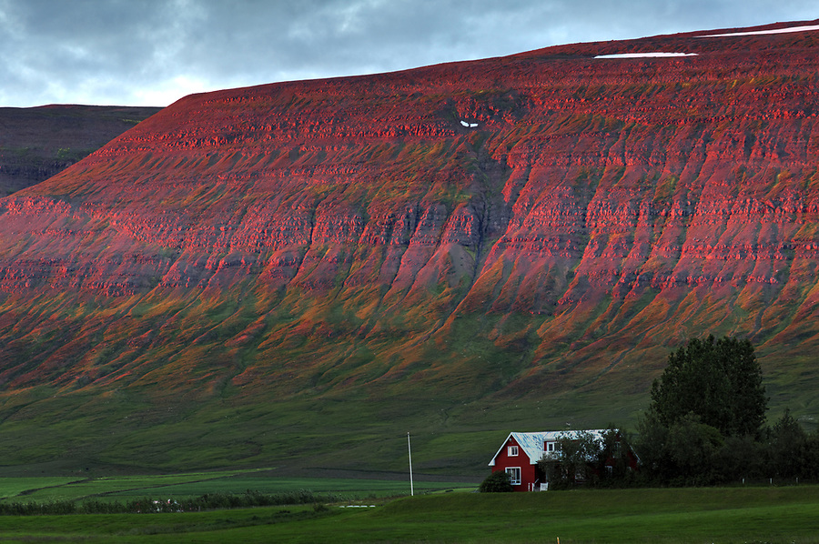 Sunset ablaze on cliffs of Sigtunafjall mountain above farmhouse, Akureyri, North Iceland, Iceland