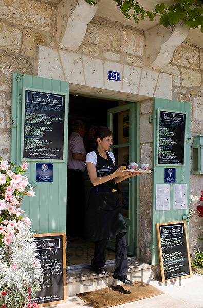 Waitress serving at French outdoor cafe in tourist town Brantome in the Northern Dordogne, France
