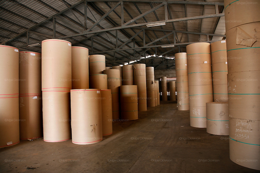 Rolls of recycled paper cardboard, for the interior of corrugated cardboard boxes, is stacked up waiting for cutting. Recycling factory for cardboard and waste paper on the outskirts of Phnom Penh. This is the biggest recycling factory for cardboard in Cambodia. The paper is mixed with water, into mulch, then the sticky mixture is laid up a belt which goes through various drying and cleaning procedures. The end product, a grey coloured paper is used primarily in corrugated cardboard filling. However most of the carboard is exported to Thailand and Vietnam