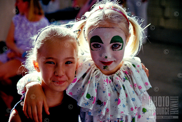 """Two young girls, one wearing a clown costume, smile at the """"""""First Night"""""""" event on Oahu."""