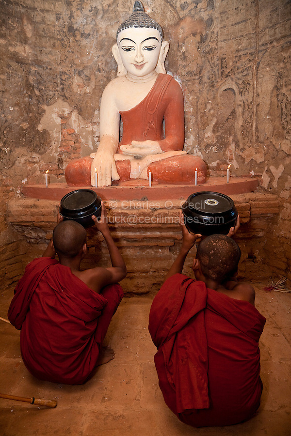 Myanmar, Burma. Bagan.  Two Young Novice Monks Praying in front of Buddha Statue.