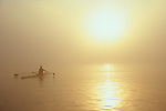 Woman rowing a single racing shell in fog at sunrise. Seattle,