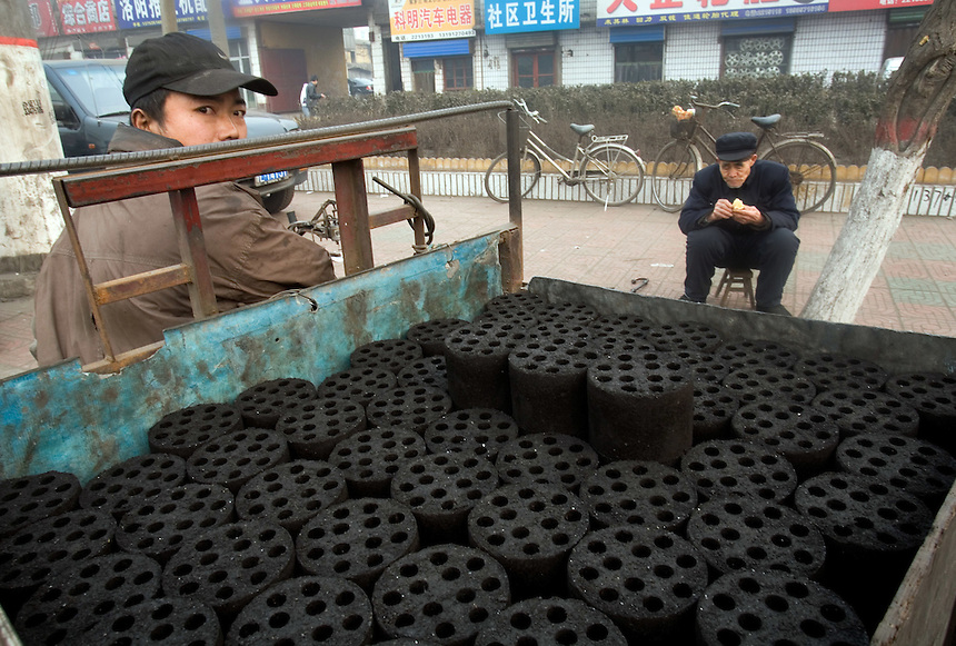 A vendor sells coal bricks used for warming homes and cooking, on a Linfen street.