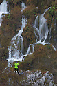 A series of waterfalls known as 'Sastavci' that cascade between mountain lakes, with photographer in foreground. Plitvice Lakes National Park, Croatia. November.