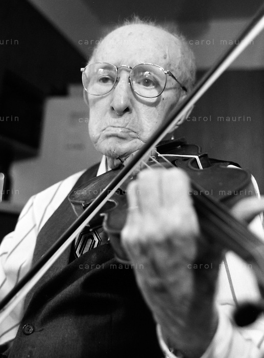 Elderly Caucasian man with big glasses concentrating on playing the violin.