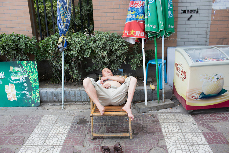 A man sleeps on a lawnchair on a sidewalk next to an icecream freezer in Xian, Shaanxi, China.