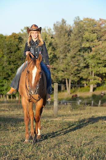 Girl riding horse in sunset farm landscape, late summer evening, bue eyed blonde cowgirl, Pennsylvania, PA, USA.
