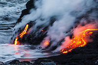 Steam rises as glowing lava meets the Pacific Ocean, Big Island of Hawai'i.