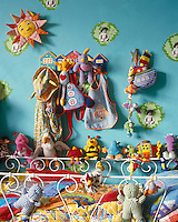 A multi-coloured collection of soft toys sit around the edge of the cot in this child's bedroom