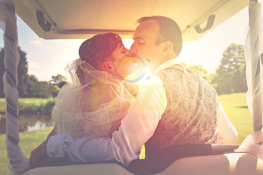 newlyweds kissing on golf buggy, Bicester Hotel, Golf and Spa, Oxfordshire