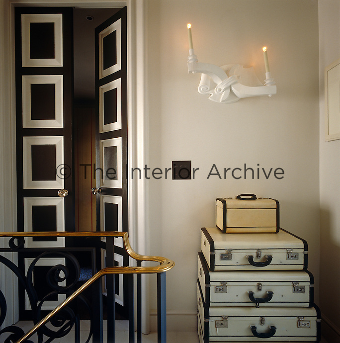 An unusual sconce above a stack of vintage suitcases heralds a doorway on this elegant landing