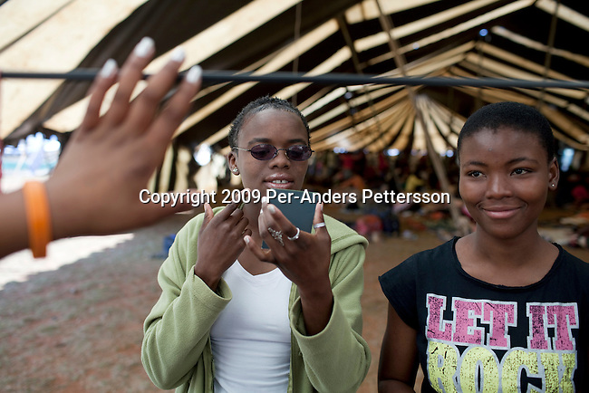 LUDZIDZINI, SWAZILAND - AUGUST 29: Unidentified girls put on makeup before a traditional Reed dance ceremony at the Royal Palace on August 29, 2009, in Ludzidzini, Swaziland. About 80.000 virgins from all over the country attended this yearly event, which goes on for a week and which is the biggest in Swazi culture. Many of the girls stayed in tents and slept on the ground. It was founded to celebrate the beauty of Swazi women and girls. King Mswati III, and absolute monarch, was born in 1968 and he has 14 wives and many children. The king danced with his men in front of the 80.000 girls. Many of the girls hope to get noticed by the king and to be chosen as a future wife, a ticket from poverty and into a life of privilege and luxury. The country is one of the poorest in the world and it is struggling with a high prevalence of HIV-Aids and severe poverty. (Photo by: Per-Anders Pettersson)...