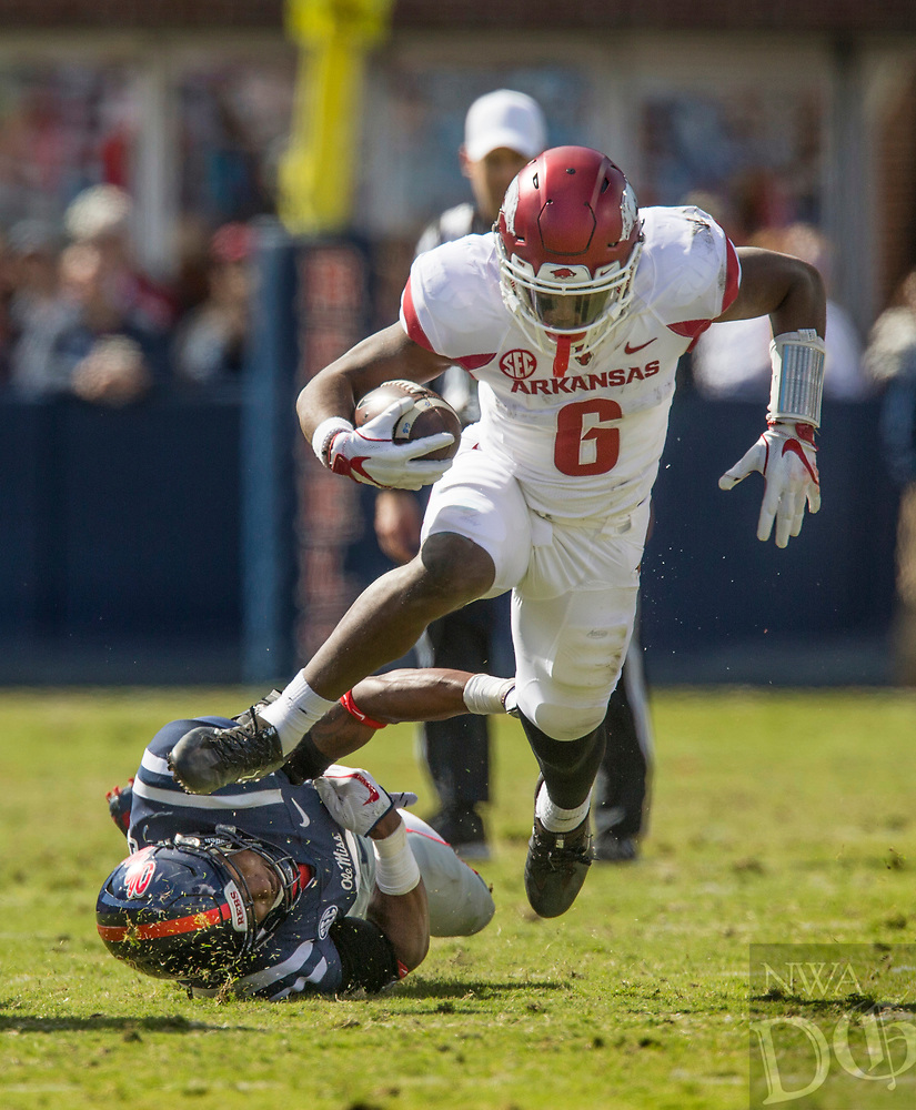 Hawgs Illustrated/BEN GOFF <br /> T.J. Hammonds, Arkansas running back, breaks the tackle of DeMarquis Gates, Ole Miss linebacker, on a run in the second quarter Saturday, Oct. 28, 2017, at Vaught-Hemingway Stadium in Oxford, Miss.