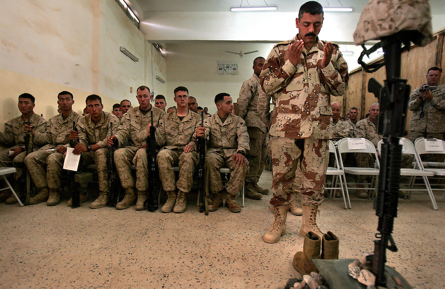 An Iraqi Army captain stands in prayer at a memorial service for Lance Corporal Miguel Terrazas killed in action by an IED in Haditha, Iraq on Nov. 19, 2005. The service was held at the company's firm base on Tues. Nov. 29, 2005.
