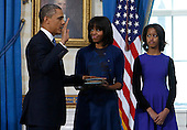 United States President Barack Obama (L) takes the oath of office from U.S. Supreme Court Chief Justice John Roberts as first lady Michelle Obama holds the bible and  daughter Malia looks on in the Blue Room of the White House in Washington, January 20, 2013. .Credit: Larry Downing / Pool via CNP