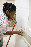 Student doing a course in tiling.  Able Skills in Dartford, Kent, runs courses in construction industry skills like, bricklaying, carpentry and tiling.