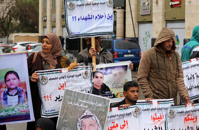 Palestinian families of martyrs, hold banners during a protest to demand their salaries, in front of Red cross office, in Gaza city, on March 28, 2016. Photo by Mohammed Asad
