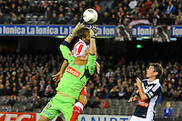MELBOURNE, AUSTRALIA - MAY 19: Lawrence Thomas of the Victory is fouled by Olof Mellberg of Olympiakos during the match between Melbourne Victory and Olympiakos FC at Etihad Stadium on 19 May 2012 in Melbourne, Australia. (Photo Sydney Low / AsteriskImages.com)