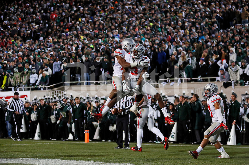 Ohio State Buckeyes wide receiver Michael Thomas (3) celebrates a 79-yard touchdown with running back Ezekiel Elliott (15) during the second quarter of the NCAA football game at Spartan Stadium in East Lansing, Michigan on Nov. 8, 2014. (Adam Cairns / The Columbus Dispatch)