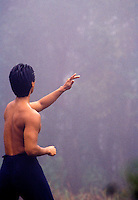 Shirtless man, viewed from behind, practicing Tai Chi in the mist at Kokee State Park, Kauai