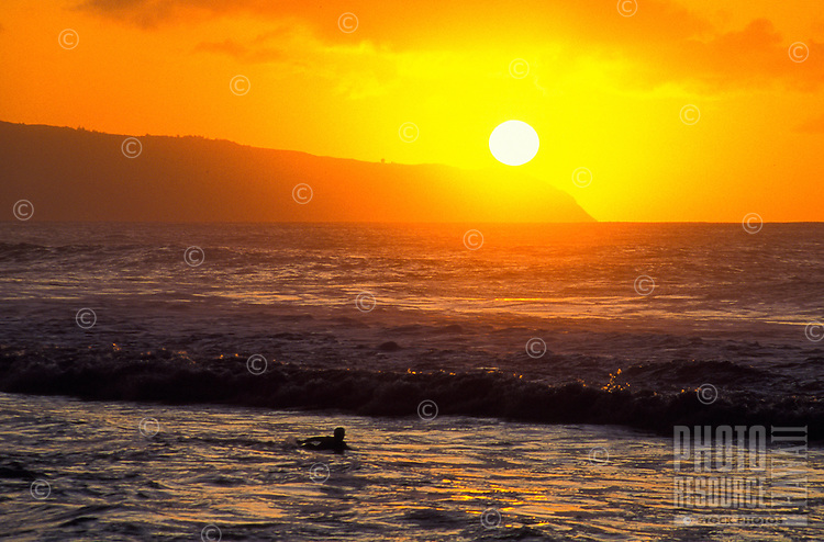 A surfer paddles out in the glowing sunset for a last wave at Kaena Point on the north shore of Oahu.