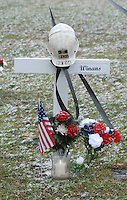 A miner's helmet sits atop the cross for Sago miner Marshall Winans at the memorial on the county courthouse lawn in Phillipi, WV Friday, Jan. 6, 2006. Winans is one of the 12 miners killed in the Sago mine explosion. (Gary Gardiner/EyePush Newsphotos)<br />