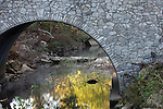 A stone arched bridge over a quaint quite creek  Fall Creek Bridges 1994