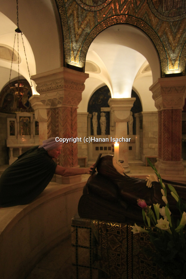 Israel, Jerusalem, a pilgrim by the statue of Mary in eternal sleep on Assumption Day at the Dormition Church on Mount Zion
