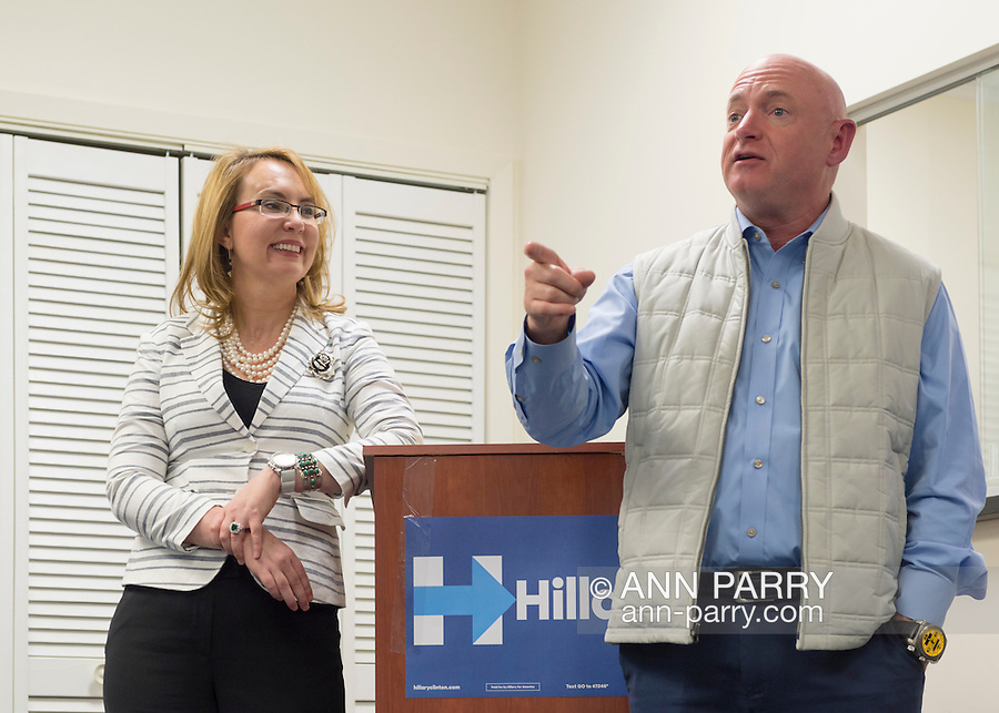 Garden City, New York, USA. 17th April 2016. GABBY GIFFORDS, former United States Congresswoman, smiles at her husband MARK KELLY, former NASA astronaut, as he speaks about the importance of GOTV, Getting Out The Vote for Hillary Clinton - including because of Clinton's strong position on stricter gun control legislation - at the Canvass Kickoff at the Nassau County Democratic Office in Garden City. After Kelly then Giffords spoke, they posed for photos with volunteers who attended the campaign Official Event. Giffords survived an assassination attempt near Tuscon, Arizona, during her first 'Congress on Your Corner' event in January 2011. Kelly commanded the final flight of the Space Shuttle Endeavor in May 2011.