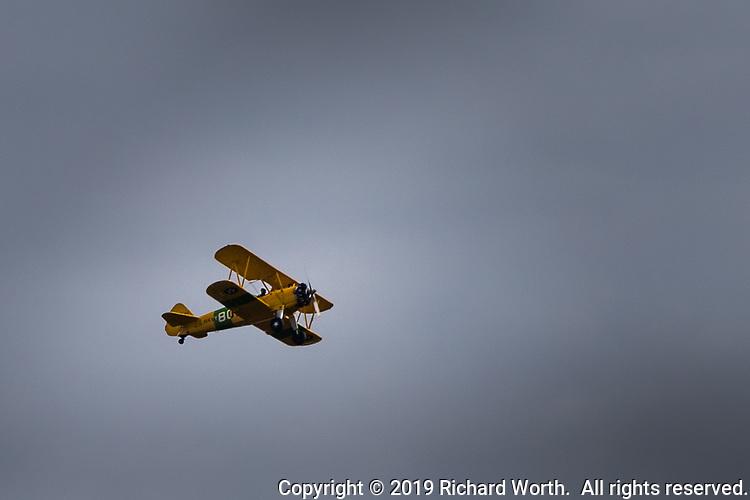 A yellow biplane circles the sky over the Duck Pond community park in San Lorenzo, California near San Francisco Bay.