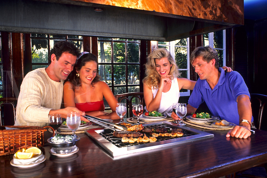 Young couples share the cuisine at a table side restaurant.