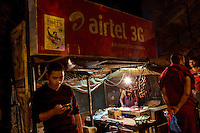 A man looks at his mobile phone next to a food stall in the Manaju Ka Tila district, a Tibetan refugee neighborhood, in Delhi where Tigers parts are traded according to the Wildlife Crime Control Bureau.