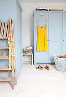A bright yellow nightdress hangs from a powder blue wardrobe in the bedroom