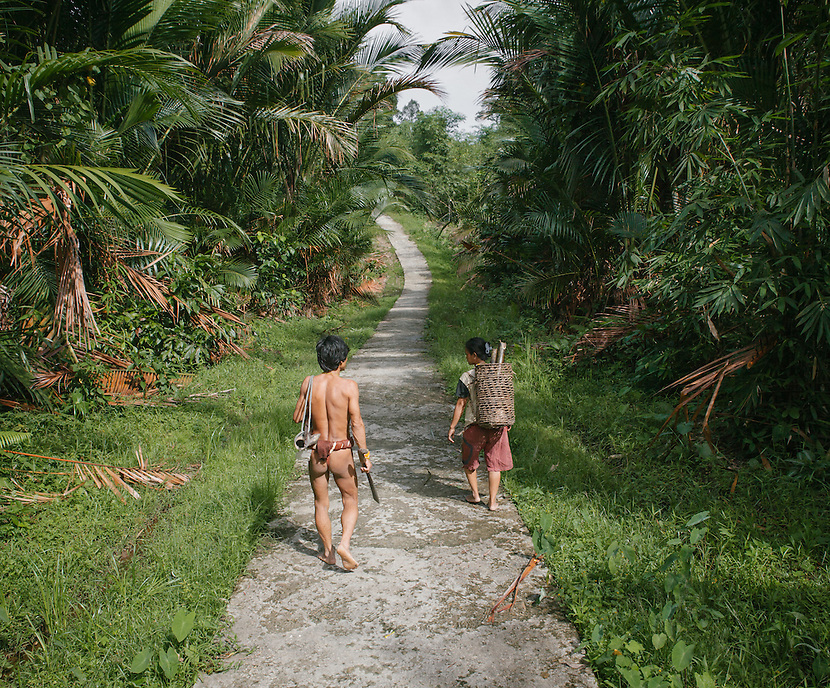 A Mentawai couple walking through the concrete pathway which now passing their village, Ugai. The Mentawai are the tribes living traditionally in the island of Siberut, Indonesia. Here, where the changes came slow, some of the people are still living like their ancestors did centuries ago. They s till practice ancient religion called Arat Sabulungan, which believe that everything in the forest has a spirit.