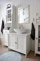The bathroom is furnished with simple IKEA pieces that complement the old tongue and groove wall panelling