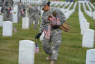 May 23, 2013  (Arlington, Virginia)  Staff Sgt. Dejesus, of the 3rd U.S. Infantry Regiment (the Old Guard), places an American flag before a gravestone at Arlington National Cemetery. The annual tradition, known as Flags In, honors every fallen soldier's grave with a flag.  (Photo by Don Baxter/Media Images International)
