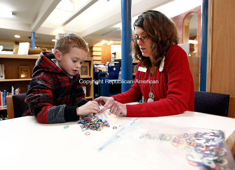 Thomaston, CT- 16 January 2014-011614CM01-  Denise Butwill, right, children's librarian for the Thomaston Public Library works with Quentin Greatorex, 7, of Thomaston, on a rubber band craft project at the library on Thursday.  Butwill said the craft program allowed children to make bracelets, rings, necklaces and other types of jewelry.  The library holds after school programs Monday through Thursday. The next program will be on Monday at 2 p.m.  The library will show the movie, Despicable Me 2 inside the community room.   For a list of events, logon to the web and go to http://www.thomastonlibrary.org.  Christopher Massa Republican-American