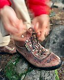 USA, California, Yosemite National Park, tying hiking boot laces before embarking on a day hike