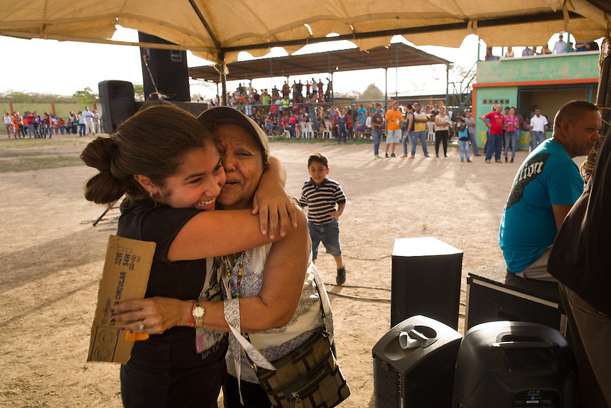 A winning embrace during a community bingo game at the local baseball stadium in Pueblo Nuevo on Venezuela's Paraguaná Peninsula, Dec. 13, 2015. The remote desert peninsula in the Caribbean Sea lays bare the effects of Venezuela's politicized economy after 17 years under Hugo Chavez and successor Nicolas Maduro. Contestants filled in bingo sheets in hopes of some cooking oil or bread.