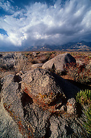 742900228 massive cloud formations from a gathering storm form over the eastern sierras mountain range and frame large granite boulders in kern county california
